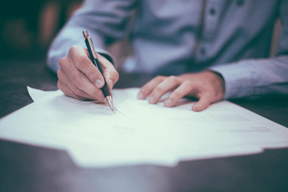 Férfi kék ingben ül az asztalnál és papírokat ír alá.