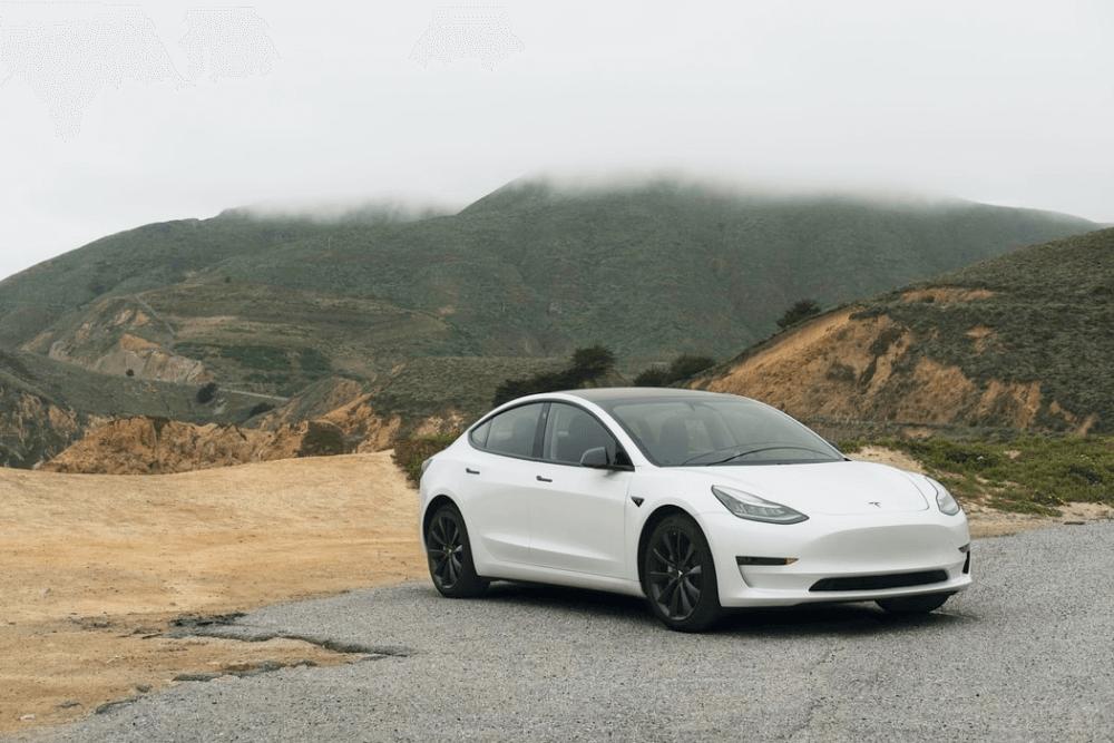 Út szélén álló fehér elektromos Tesla, háttérben hegyek.