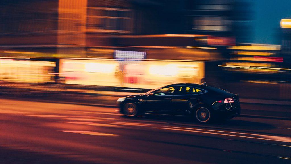 Hibrid autó közlekedik az éjszakában, körülötte elmosódik a környezet.