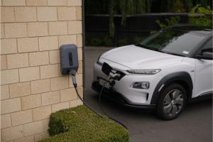 Fehér plug-in hibrid autó töltése.