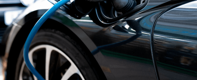 Egy fekete plug-in hibrid autó épp töltés alatt.