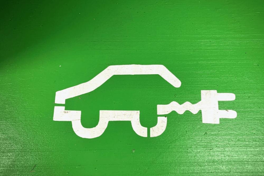 Zöld autó festett ikonon való ábrázolása: fehér autó töltőkábellel, zöldre festett falon.